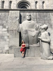 Tatevik standing in front of a large statue of a sitting man and a standing person