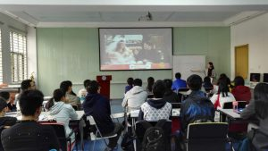 A classroom full of students watching something on a projected screen